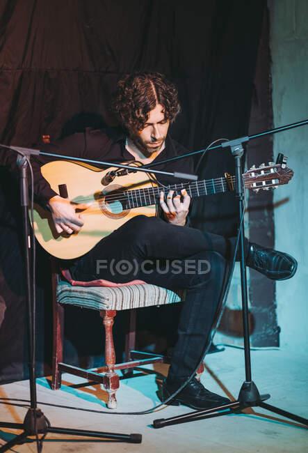 Musicista ispanico in abito nero seduto con le gambe incrociate su sedia di legno vicino al microfono mentre suona la chitarra sulla piattaforma teatrale — Foto stock