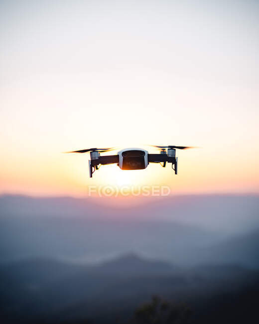 Drone flying in sunset sky with defocused mountains on background — Stock Photo