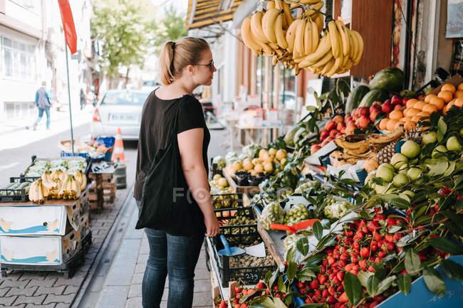 Vista lateral da fêmea positiva em desgaste casual e óculos de sol perto do balcão de frutas no mercado turco e explorar mercadorias enquanto caminha pelas ruas da cidade — Fotografia de Stock