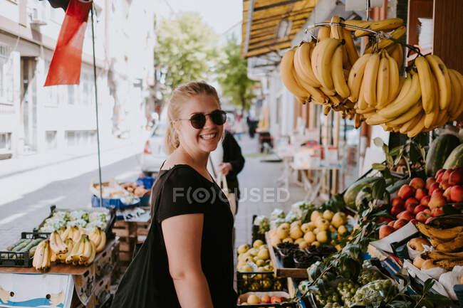 Vista lateral da fêmea positiva em roupas casuais e óculos de sol olhando para a câmera perto do balcão de frutas no mercado turco e explorando mercadorias enquanto caminha pelas ruas da cidade — Fotografia de Stock