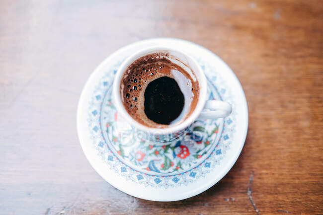 From above of aromatic black hot Turkish coffee in fragile traditional white cup and saucer painted with oriental pattern standing on wooden table — Stock Photo