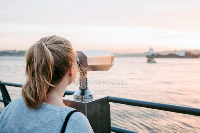 Back view of anonymous female traveler in casual outfit standing on embankment and admiring view of colorful amazing sunset — Stock Photo