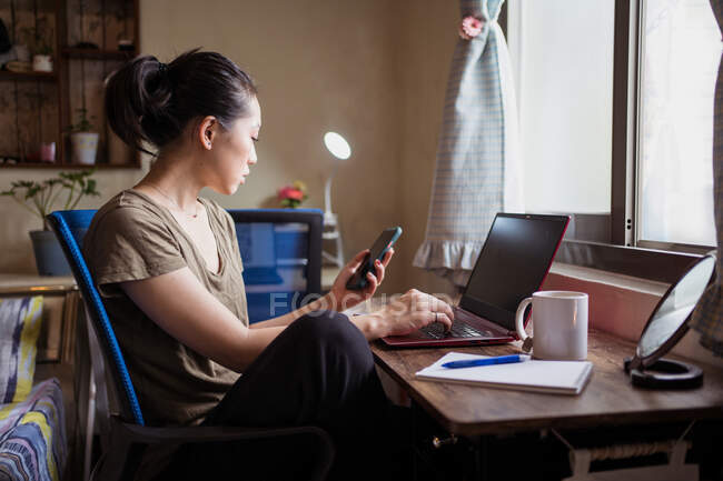 Side view of Asian female freelancer in casual t shirt sitting at table and browsing computer working on project online at home while texting on the smartphone — Stock Photo