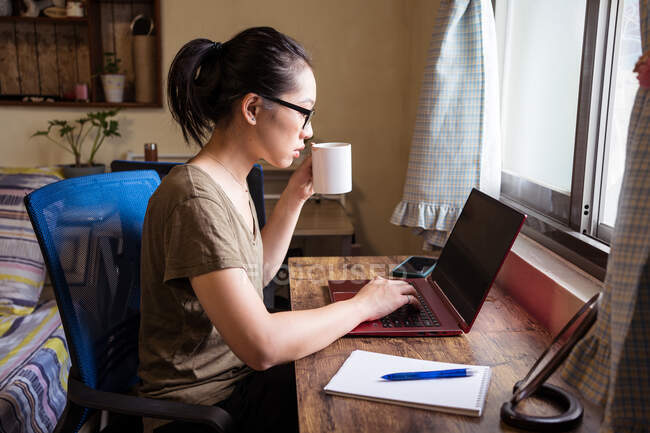 Side view of Asian female freelancer in casual t shirt and eyeglasses sitting at table and browsing computer while working on project online at home and drinking hot beverage from a mug — Stock Photo
