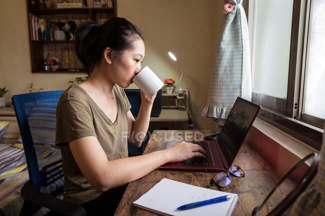 Сторона зору азіатської жінки-фрилансер у повсякденній футболці, яка сидить за столом і переглядає комп'ютер під час роботи над проектом в Інтернеті вдома і п'є гарячий напій з кухлі. — стокове фото