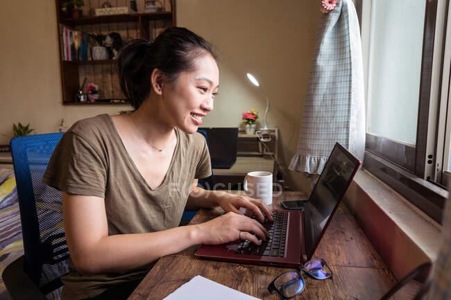 Vista lateral do freelancer feminino asiático em camiseta casual e óculos sentados à mesa e computador de navegação enquanto trabalhava no projeto online em casa — Fotografia de Stock