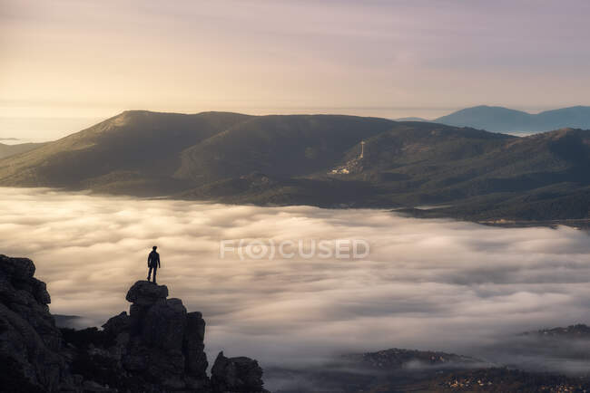 Remote unrecognizable hiker standing on edge of rock above cloudy foggy valley and admiring magnificent mountain landscape in morning — Stock Photo