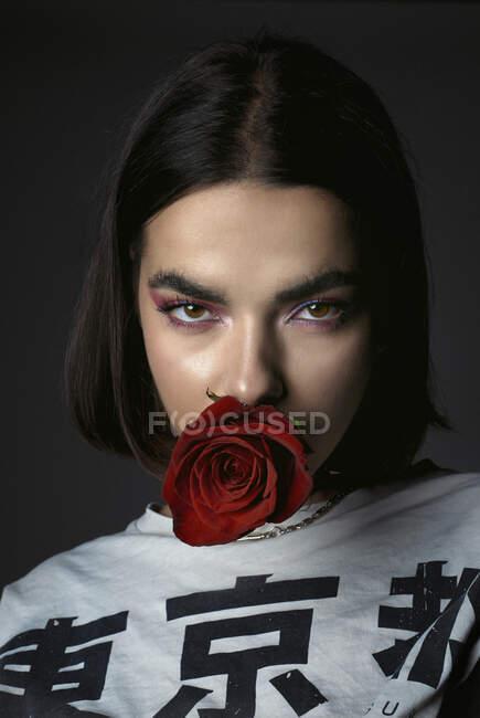 Провокационная юная леди в стильной футболке с красным цветущим бутоном розы во рту, заманчиво глядя в камеру — стоковое фото