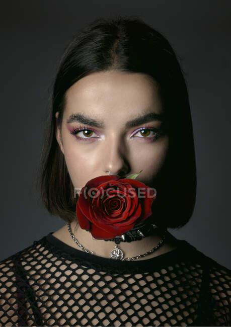 Очаровательная бунтарка с красной розой смотрит в камеру. — стоковое фото
