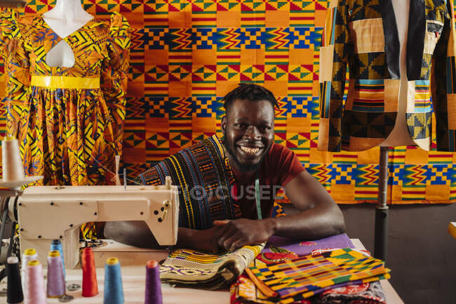 Happy black male tailor creating national costume of colored fabric with African patterns on sewing machine while sitting on background of colored African material and mannequin in sewing workshop — Stock Photo