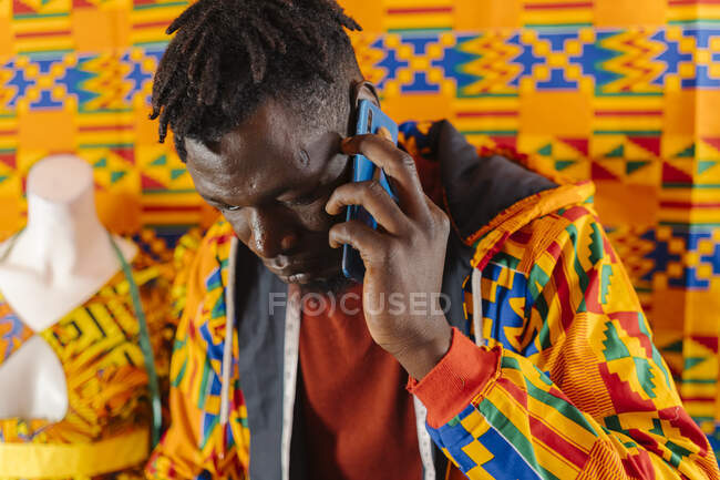 Concentrated young African American male in colorful clothes standing near table and answering phone call while cutting fabric during working process in creative studio — Stock Photo