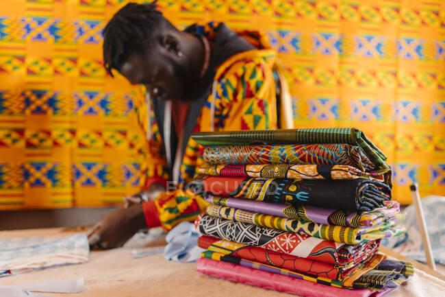 Сконцентрований молодий афроамериканець у барвистому одязі стоїть біля столу під час роботи в творчій студії. — стокове фото