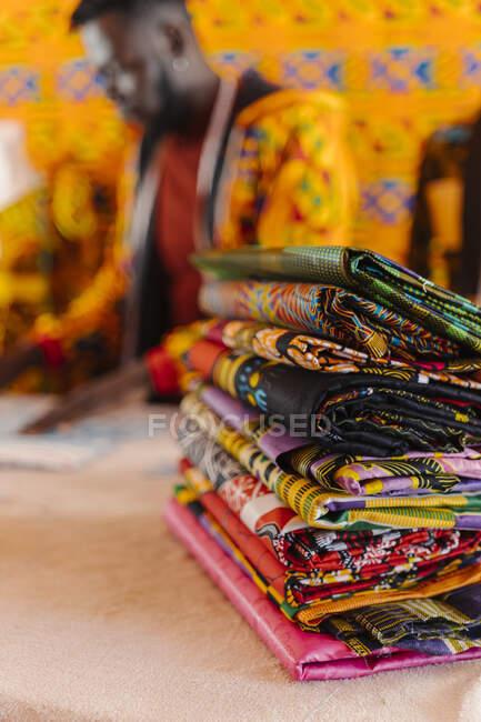 Складки багатокольорового матеріалу з африканськими традиційними візерунками розташовуються на столі на тлі розмитого чорного кравця в швейній майстерні. — стокове фото
