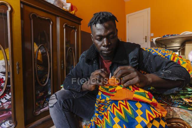 Черный серьезный парень в повседневной одежде сидит на кресле в грязной швейной мастерской и работает над платьем из цветного материала — стоковое фото