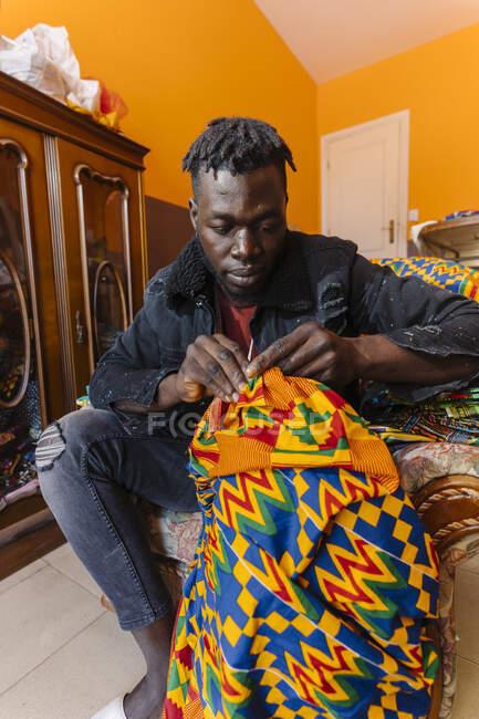 Negro chico serio en traje casual sentado en sillón en taller de costura desordenado y trabajando en vestido de material de color - foto de stock