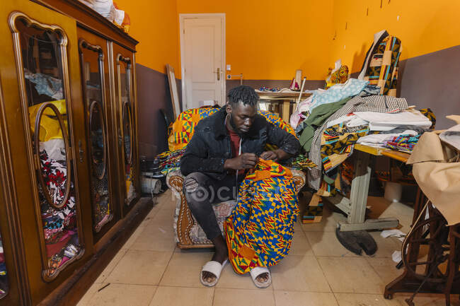 Black serious guy in casual outfit sitting on armchair in messy sewing workshop and working on dress made of colored material — Stock Photo