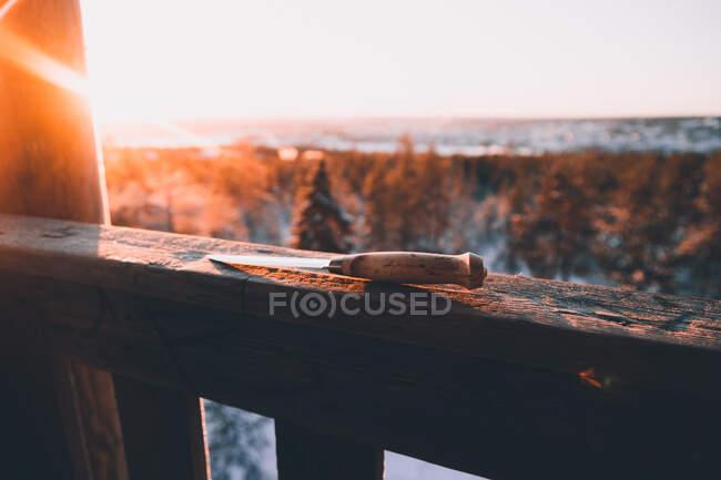 Нож с деревянной ручкой на деревянном заборе против снежного леса в солнечный зимний день в сельской местности Финляндии — стоковое фото