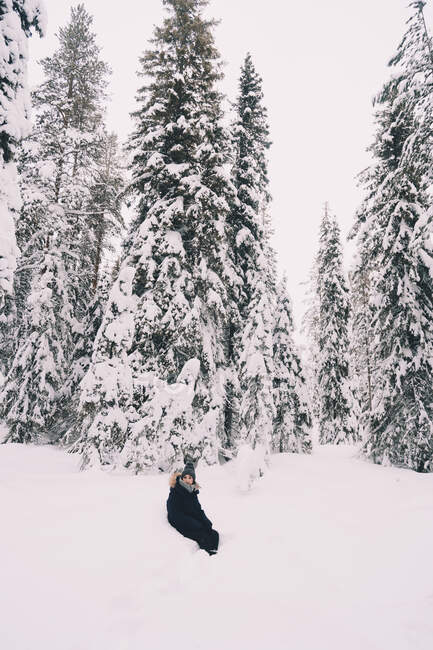 Side view of unrecognizable female traveler in warm outerwear standing on snowy path among snow covered spruce trees in winter day in Finland — Stock Photo