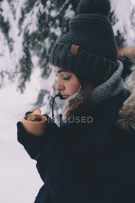 Side view of young female in warm clothes and hat with cup of hot beverage standing in snowy forest in winter day in Finnish countryside — Stock Photo