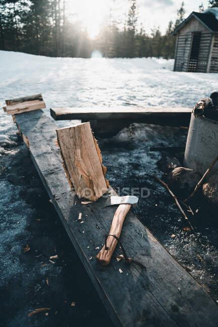 Feu de joie brûlant et rondins avec hache placés près d'une petite cabane de bûcheron dans une forêt enneigée en hiver dans la campagne de Finlande — Photo de stock