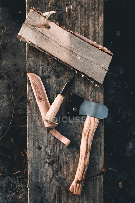 Top view of axe and knife placed on wooden rustic surface in the countryside of Finland — Stock Photo