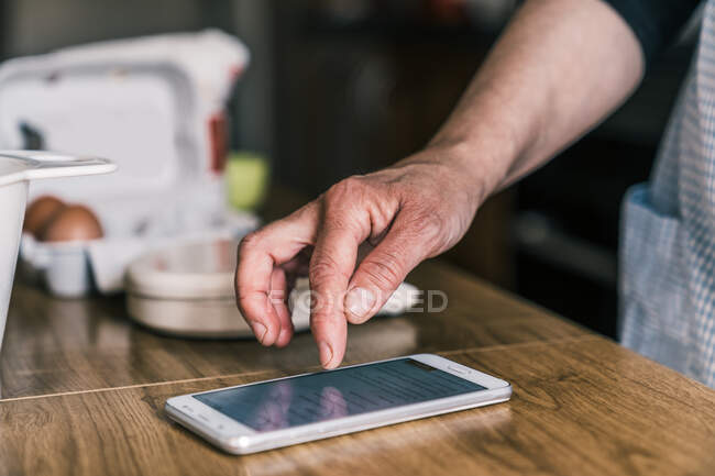 Crop anonymous mature woman in apron using smartphone and reading recipe while standing at kitchen counter with ingredients for baking — Stock Photo