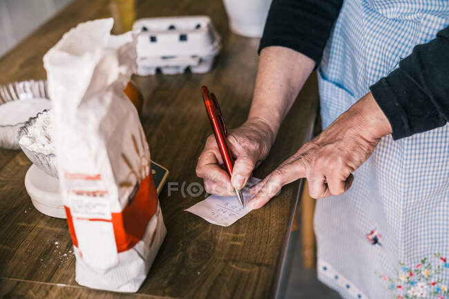 From above of crop anonymous mature female in apron making calculation on paper while preparing ingredients for pastry in home kitchen — Stock Photo