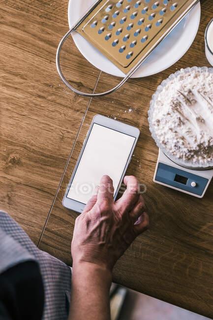 Anonymes weibliches Browserrezept auf dem Smartphone und Wiegen von Weizenmehl auf elektronischen Waagen bei der Zubereitung von Zutaten für hausgemachtes Gebäck in der Küche — Stockfoto