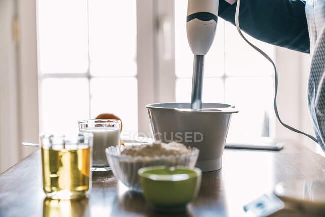 Vue latérale de la culture femme au foyer anonyme en utilisant un mélangeur tout en préparant la pâte pour les muffins sucrés au comptoir de la cuisine avec des ingrédients pour la recette — Photo de stock