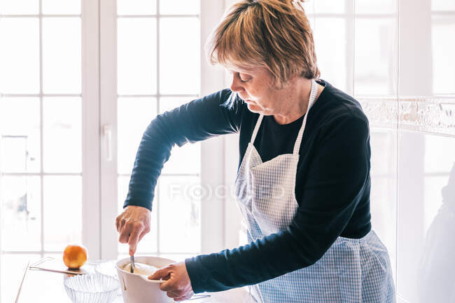 Side view of elderly female in apron standing at table in bright kitchen and mixing ingredients for muffins in plastic bowl — Stock Photo