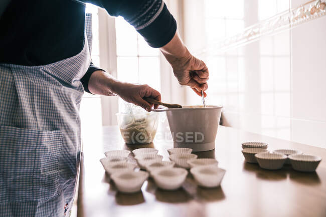 Side view of crop female confectioner wearing apron standing in kitchen at home and getting ready for pouring dough in muffin paper cases — Stock Photo