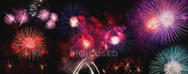 Яркие различные фейерверки, взрывающиеся на фоне черного ночного неба — стоковое фото