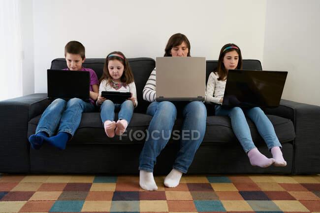 Серьезные мать и дети проводят время вместе, используя гаджеты на диване дома — стоковое фото