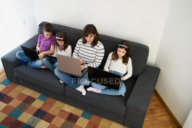 Сверху вид серьезной матери в повседневной одежде, сидящей со скрещенными ногами на удобном диване с детьми и использующей ноутбуки в гостиной — стоковое фото