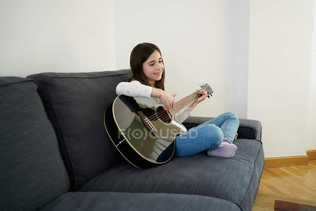 Junges Mädchen lernt Schwester auf Sofa zu Hause Gitarre spielen — Stockfoto