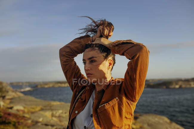 Belle jeune voyageuse en vêtements décontractés debout sur le bord de mer rocheux tenant les cheveux vers le haut avec la main dans une queue de cheval élevée pendant une journée venteuse et regardant loin rêveur — Photo de stock