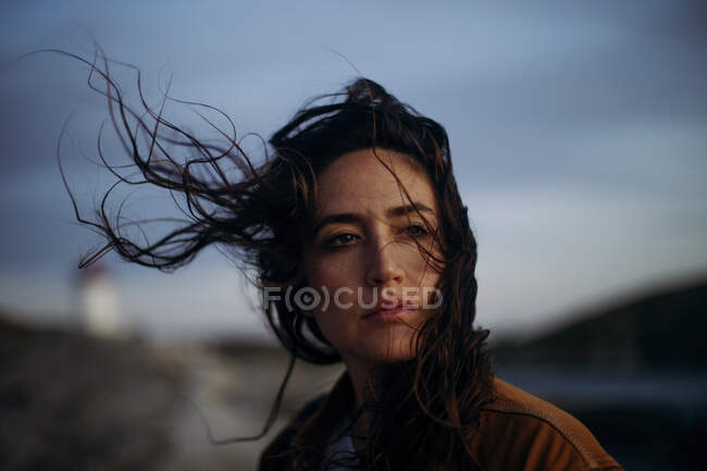 Female wearing casual clothes standing on lake shore near observation tower enjoying breeze and looking away — Stock Photo