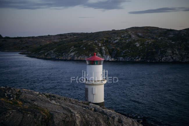 Torre di avvistamento bianca con tetto rosso e punto panoramico recintato situato sul lago vicino alle montagne grigio scuro nella giornata nuvolosa di sera — Foto stock