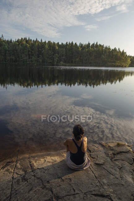From above back view of unrecognizable female wearing swimsuit sitting on rocky shore of lake and enjoying picturesque landscape of forest — Stock Photo
