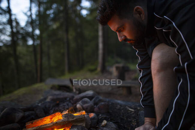 Vue latérale de l'homme tranquille assis près du feu de camp dans les bois et se réchauffer tout en profitant week-end — Photo de stock