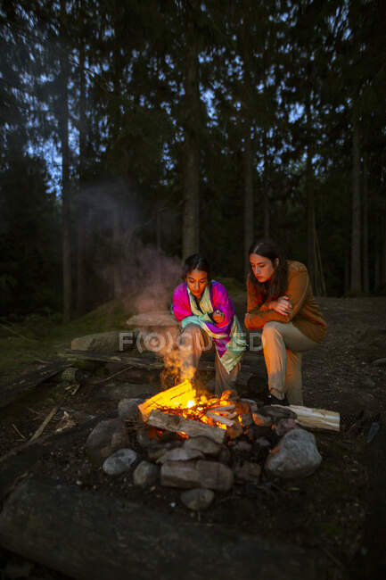 Young women in casual clothes gathering around bonfire in wood while making fire and warming up in evening — Stock Photo