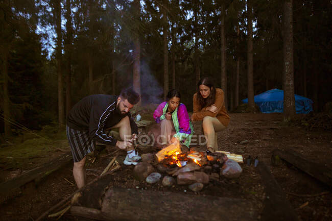 Company of friendly people in casual clothes gathering around bonfire in wood while making fire and warming up in evening — Stock Photo