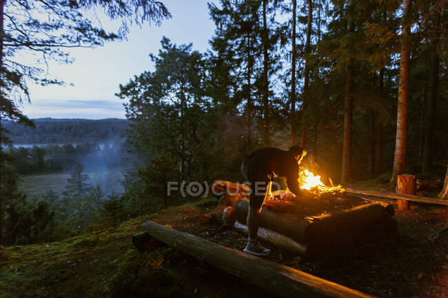 Calm male camper in casual wear standing with log near bonfire at sundown and warming up during camping in wood — Stock Photo