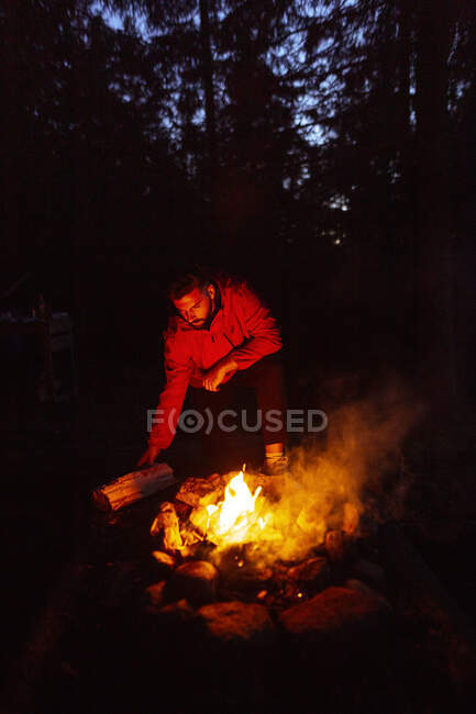 Calm male camper in casual wear standing with log near bonfire at night and warming up during camping in wood — Stock Photo