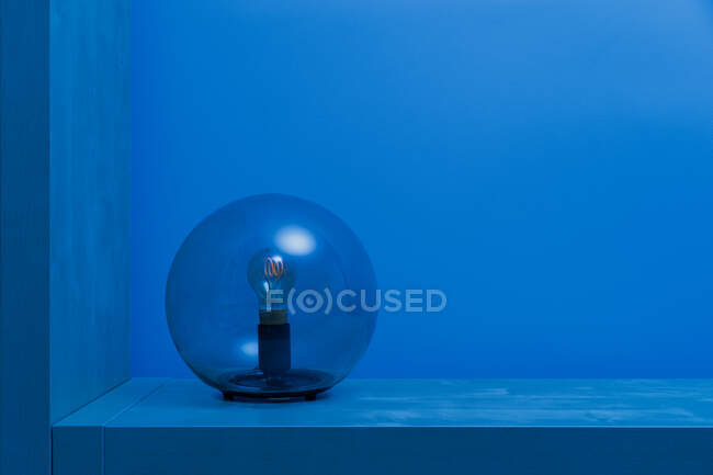 Modern turned off luminaire with light bulb inside thin transparent glass sphere in middle of shelf in blue room at dusk — Stock Photo