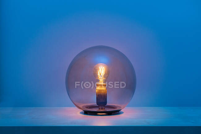 Modern turned on luminaire with light bulb inside thin transparent glass sphere in middle of shelf in blue room at dusk — Stock Photo