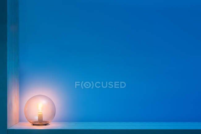 Stylish round lamp with glowing yellow light inside of glass ball locating on shelf in dark room with blue walls — Stock Photo