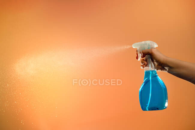 Personne anonyme avec pulvérisation en bouteille plastique pour la désinfection des surfaces pulvérisant du liquide sur fond orange en studio — Photo de stock