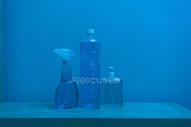 Botellas transparentes de plástico de diferentes tamaños y formas con líquido incoloro en el interior y tapas blancas ubicadas en el estante contra la pared azul - foto de stock