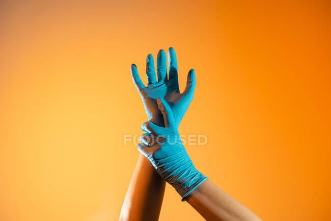 Anonymer Sanitäter in Einweg-OP-Handschuhen berührt Handgelenk auf orangefarbenem Hintergrund im Studio — Stockfoto